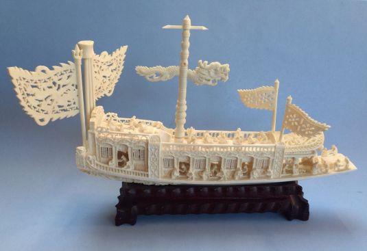 Embarcación china esculpida en marfil con mucho detalle, tiene base de madera. Procedencia: China, 1940.