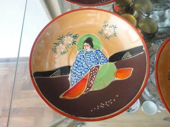 Plato de té de ceáamica Satsuma pintado a mano con los colores característicos de esta cerámica: azul, verde y rojo. Además contrasta el marrón mate con el nacarado brillante.