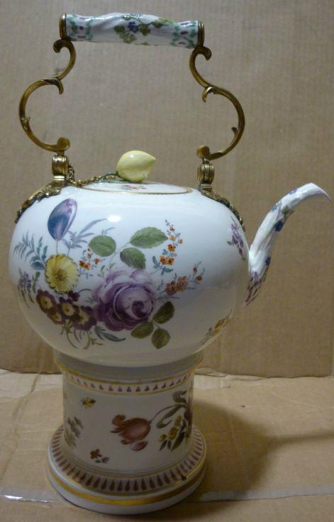 Tetera de porcelana alemana pintada a mano. El asa y cadena de la tapa son de bronce y el asa además lleva un adorno de porcelana, 1890.