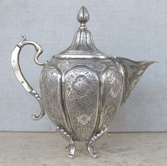 Tetera oriental de plata totalmente repujada a mano. Tiene asa de madre perla y patas de plata. 1890.
