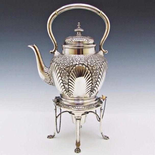 Tetera Victoriana de plata y repujada a mano. Lleva base con cadena y mechero para mantener caliente el té.