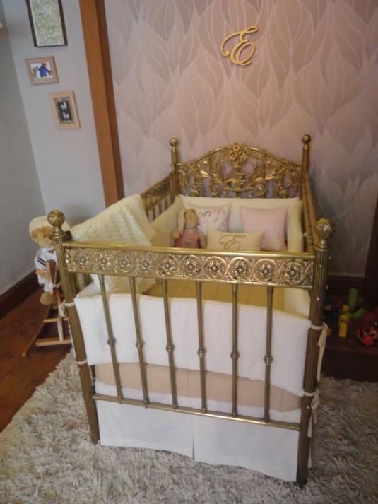Antigua cuna de bronce incorporada al diseno de la habitación infantile.