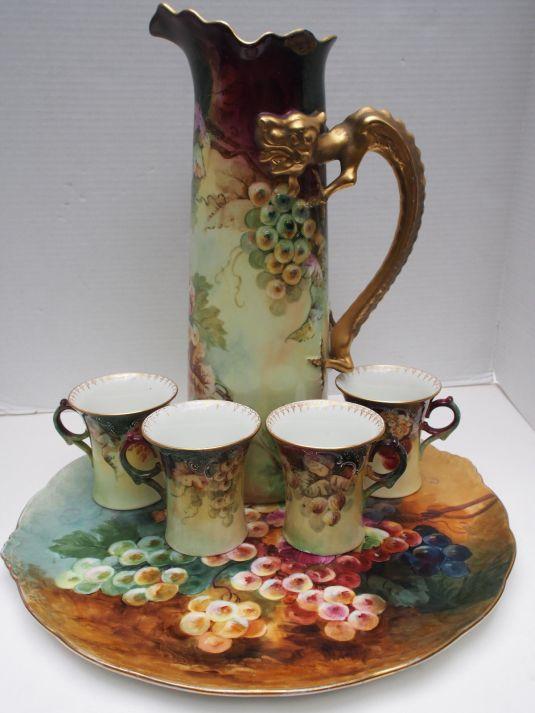 Juego de jarra, fuente y cuatro jarros con pintura a mano de bodegón. la jarra tiene un asa en forma de dragon en pan de oro. Francia, 1890.