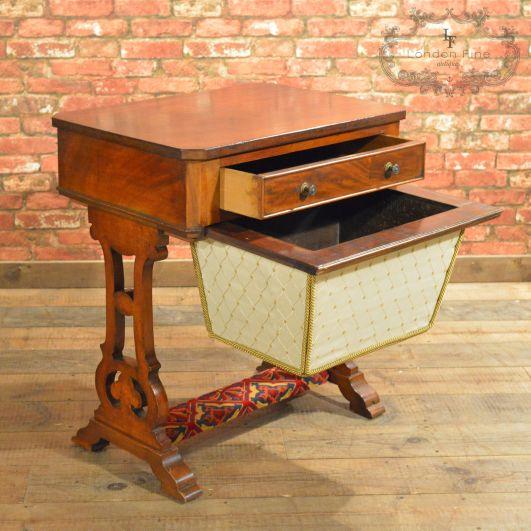 Mesa de coser vitoriana en caoba Inglaterra 1860. Se puede observar un cajón para los accesorios pequenos y un bolsón para poner telas. En la parte inferior lleva una almohadilla para los pies.