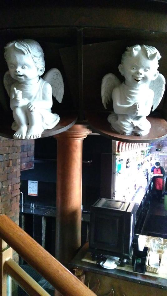Escultura del angel bueno y el malo (con cachitos).  Estos ágeles tienen luz en los ojos que se aprecia en la oscuridad.  Detalle del bar del Purgatorio.