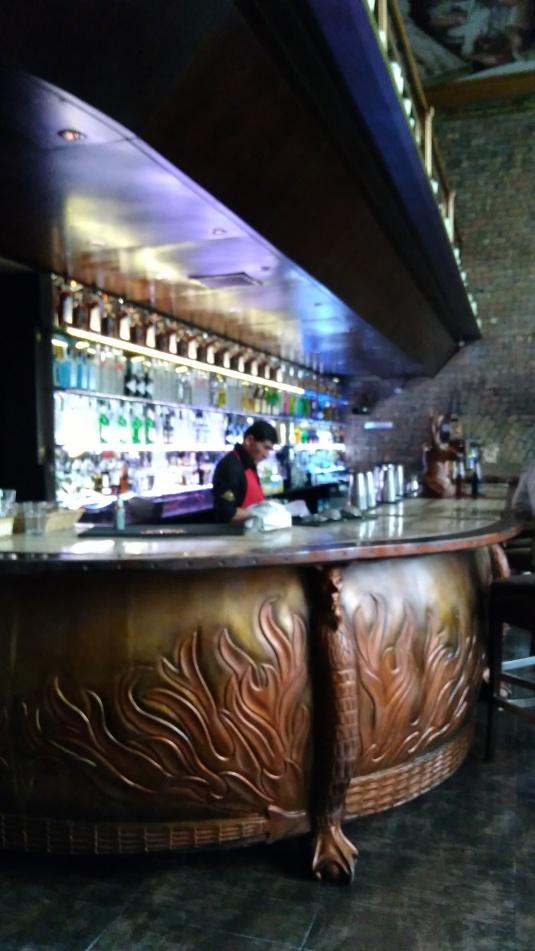 Bar de madera tallado con las flamas del infierno. No se aprecia en la foto la escultura del demonio.  Este bar está en el Purgatorio.