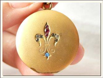 Medallón Art Nouveau de bronce enchapado en oro, decorado con flor de liz y piedritas falsas. Francia, principios 1900.