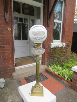 Lamparín victoriano publicitario de una fabrica de lamparines de parafina de Escocia. Tiene base con columna corintia y adorno de globo de vidrio labrado.